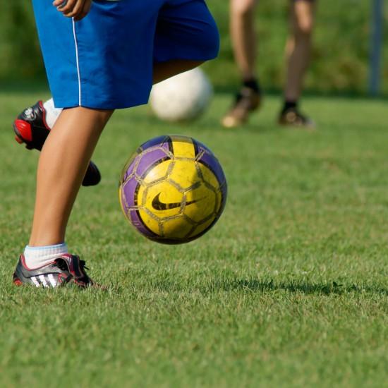 Youth kicking a soccer ball